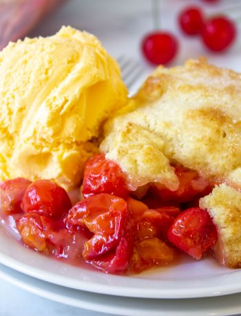 Cherry cobbler with red sour cherries topped with a scoop of vanilla ice cream.