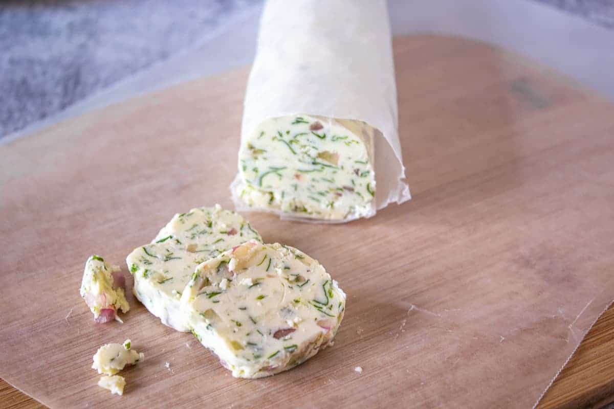 Slices of butter with herbs and shallots.