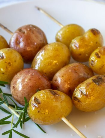 Grilled baby potatoes skewered on a stick.