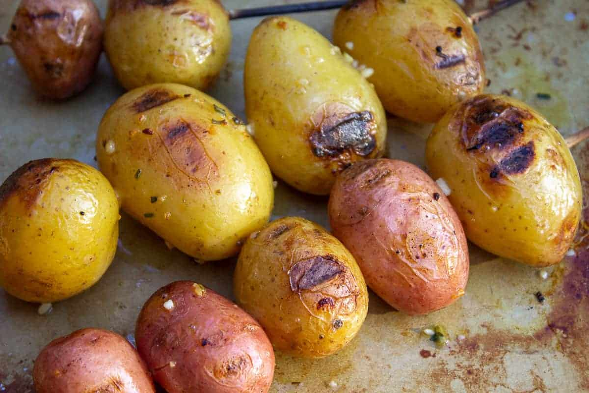 Cooked red and yellow potatoes on a baking sheet.