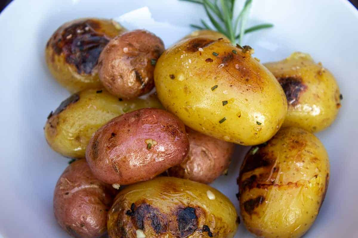 Grilled baby potatoes with a sprig of rosemary.