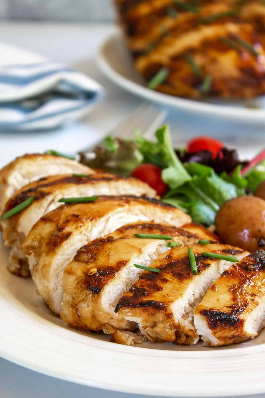 Sliced honey lemon chicken breast on a plate with a green salad.