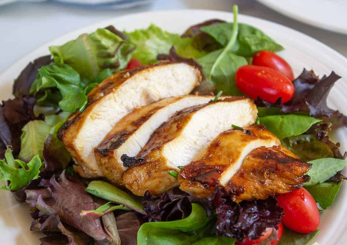 Sliced chicken breasts on top of a green salad.