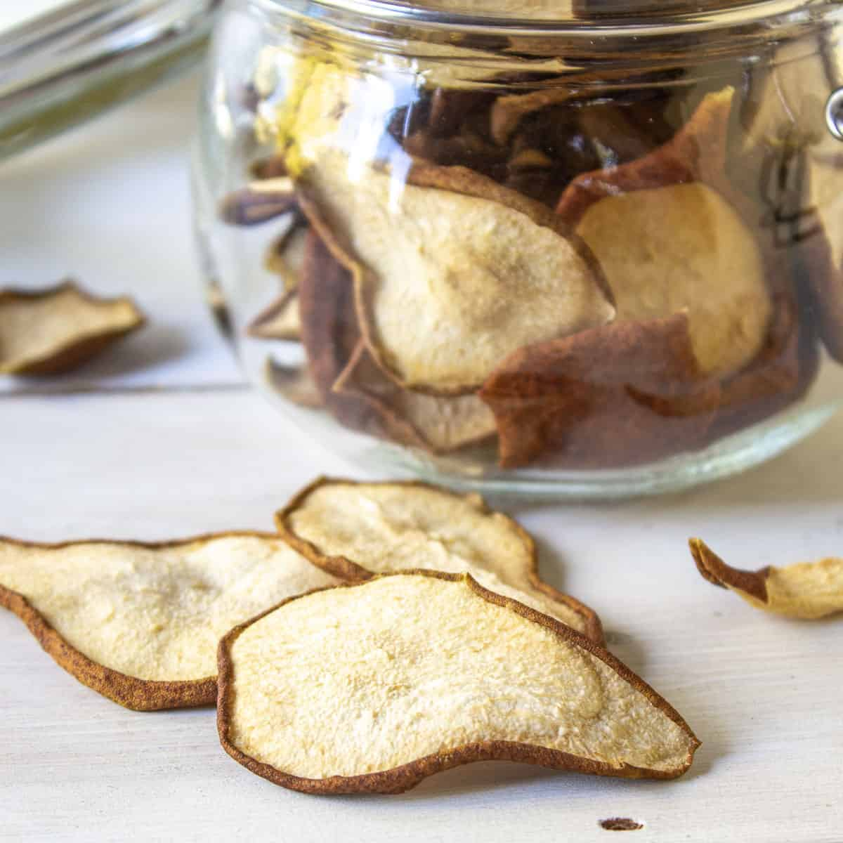 Dried pears on a board with a glass jar filled with pear chips behind them.