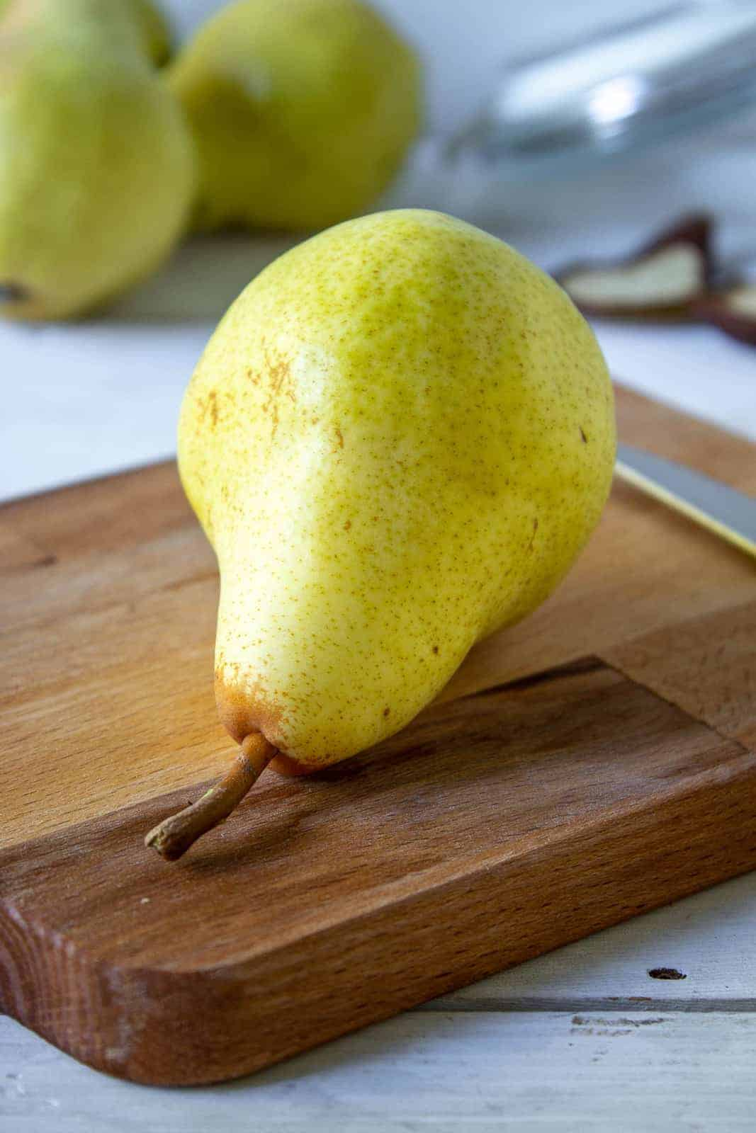 A fresh pear on a wooden cutting board.