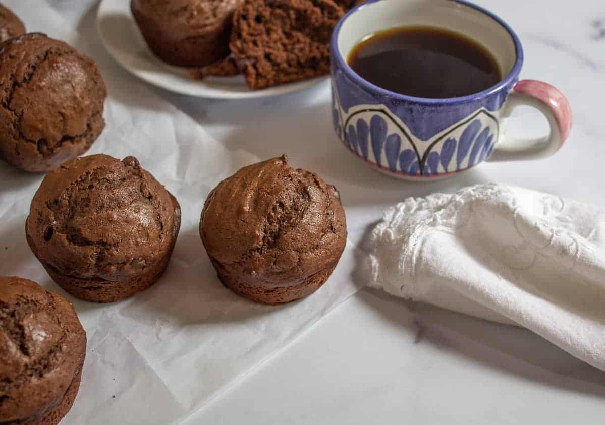 A chocolate muffin alongside a cup of coffee.