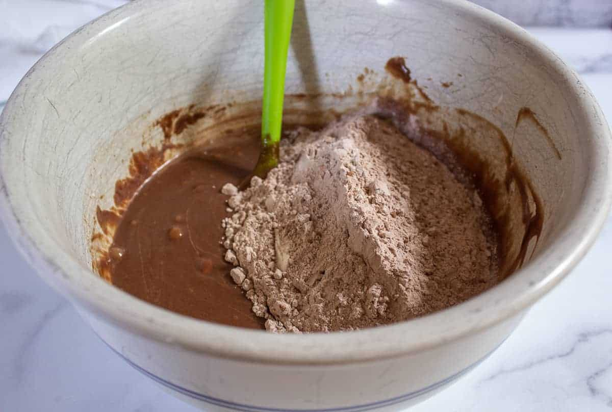Flour mixture on top of a chocolate batter in a large bowl.