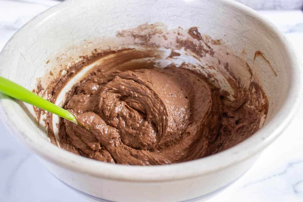 Chocolate muffin batter in a large bowl with a green spatula.