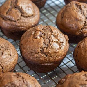 Chocolate muffins on a baking rack.