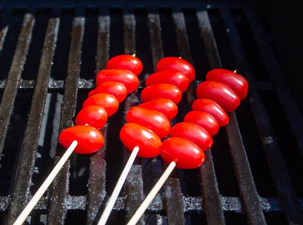Tomato skewers on a barbecue grill.