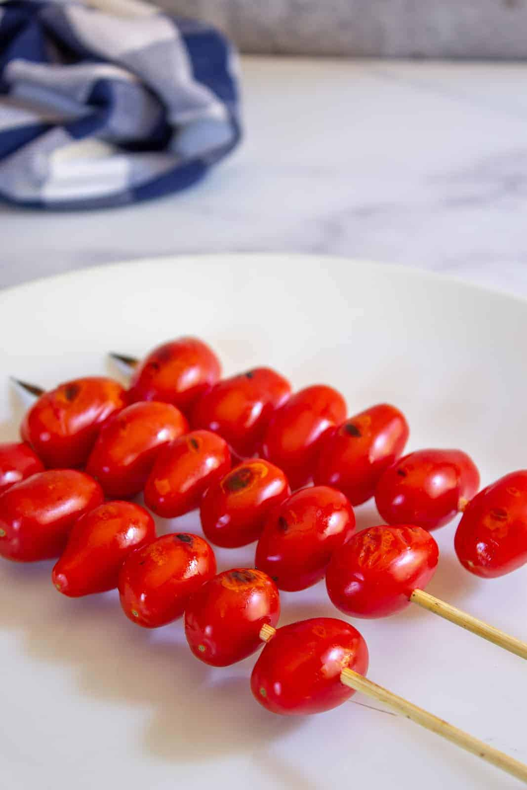 Cherry tomatoes on a wooden skewer.