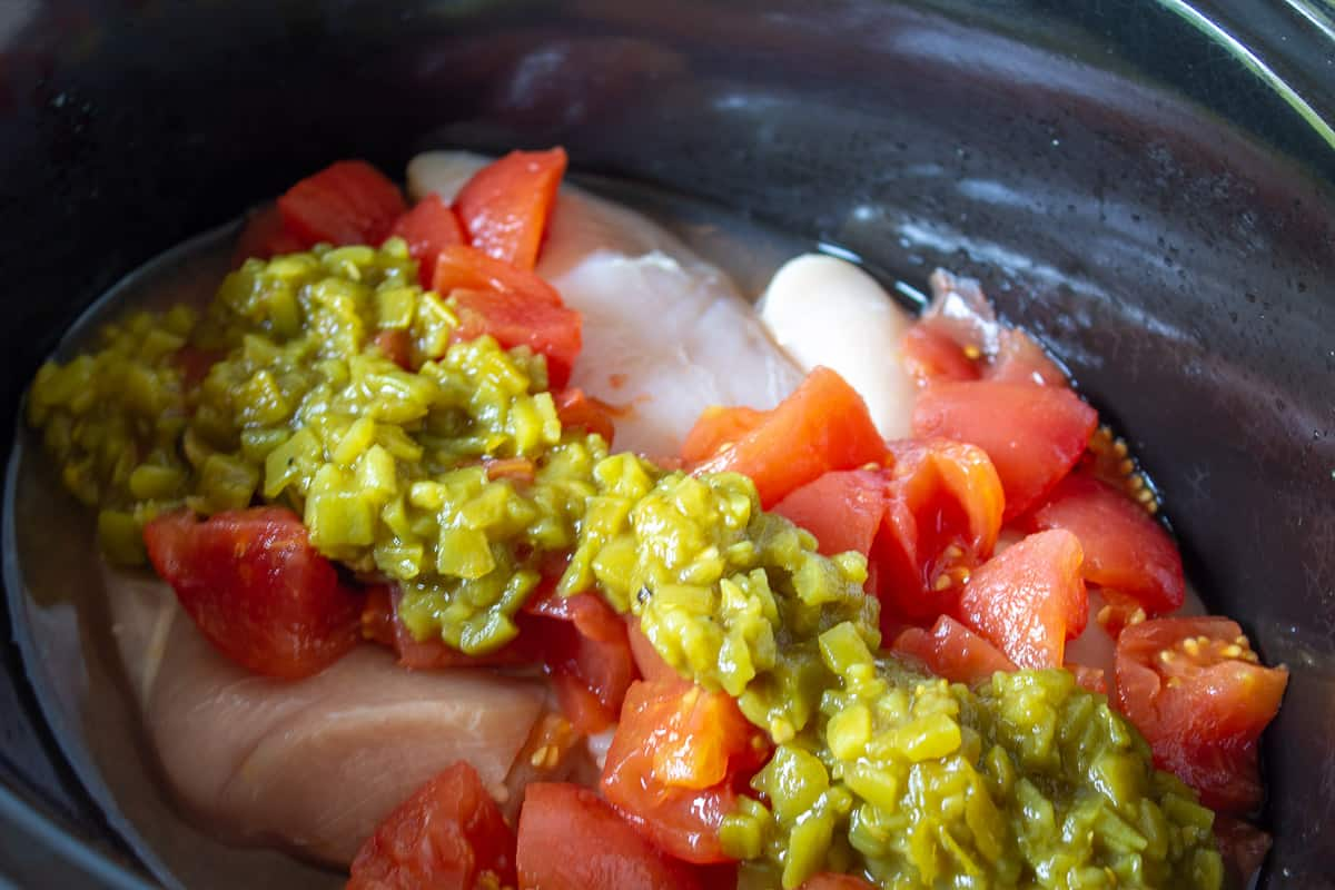 A crock pot with chicken, chopped tomatoes and green chilies.