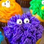 Purple, orange and blue frosted cupcakes with candy eyes.