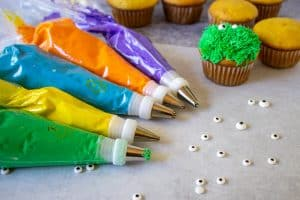 Colorful bags of frosting with different cake decorating tips.