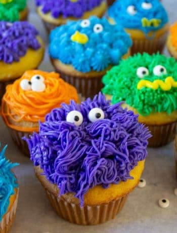 Colorful monster cupcakes with candy eyes arranged in a group.