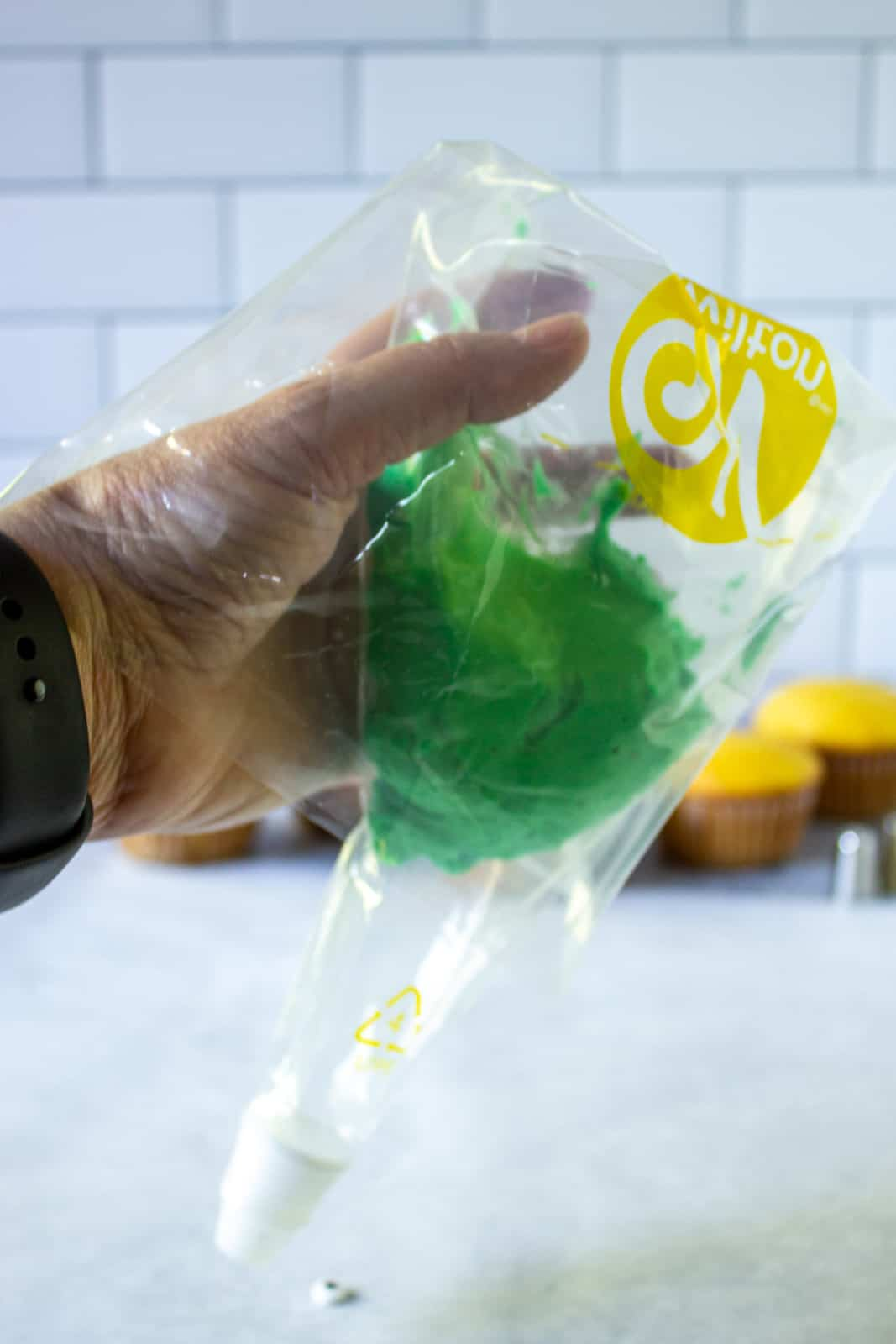 A cake decorating bag being filled with green frosting.