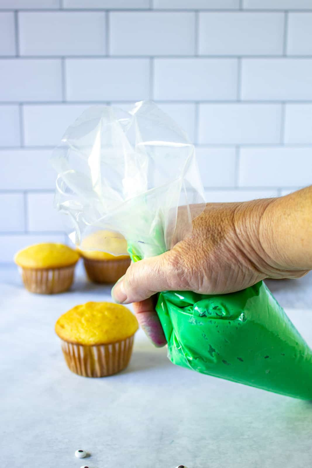 A cake decorating bag filled with green frosting.
