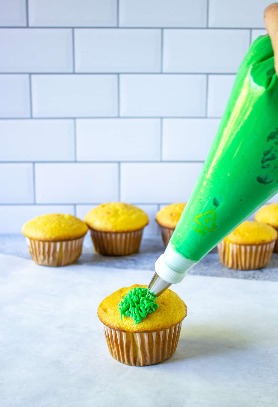 Adding green frosting to a cupcake.