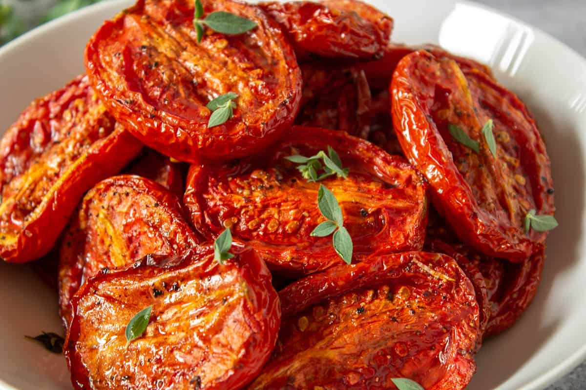 A bowl filled with oven roasted tomatoes.