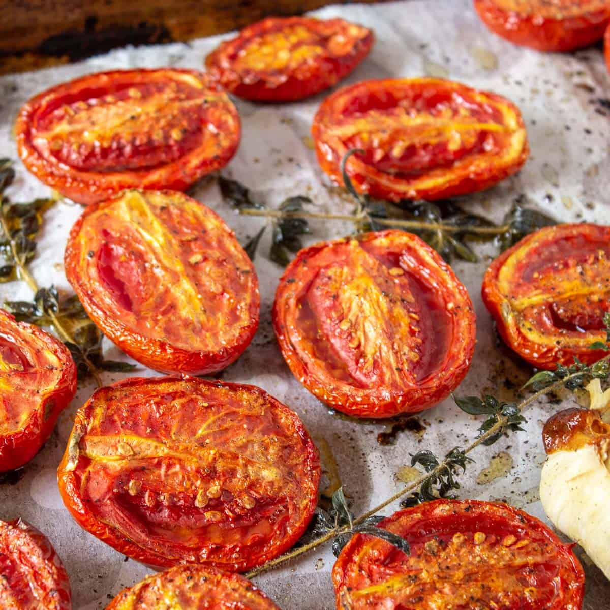 Oven roasted tomatoes with fresh herbs and garlic on a roasting pan.