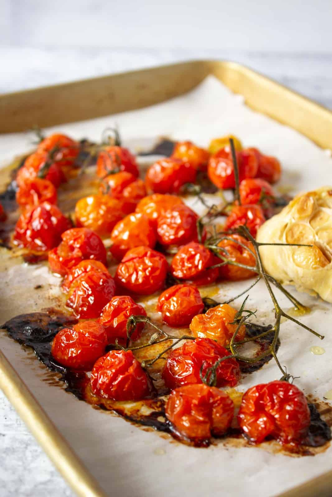A baking sheet filled with oven roasted cherry tomatoes and roasted garlic.