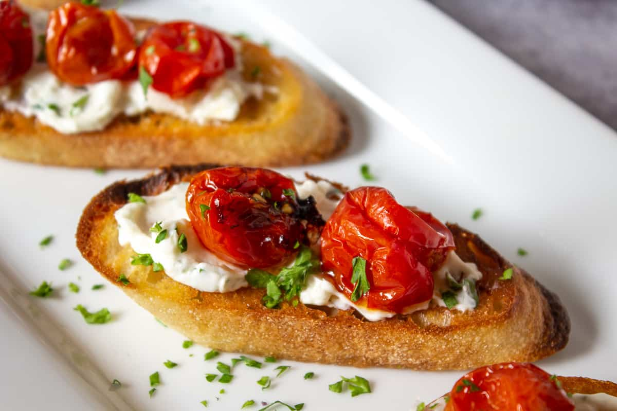 Roasted cherry tomatoes on grilled toast with creamy cheese.