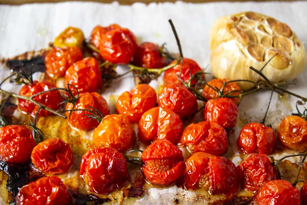 Roasted cherry tomatoes with roasted garlic on a baking sheet.