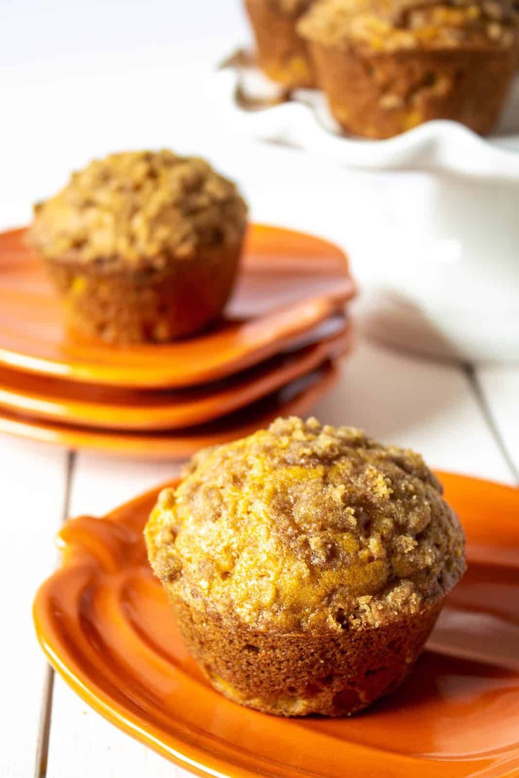 A pumpkin muffin on an orange pumpkin shaped plate.