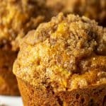 A pumpkin apple muffin on a white scalloped plate.