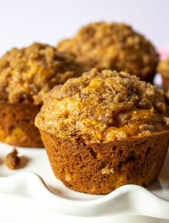 Pumpkin muffins with a streusel topping on a white cake stand.topping