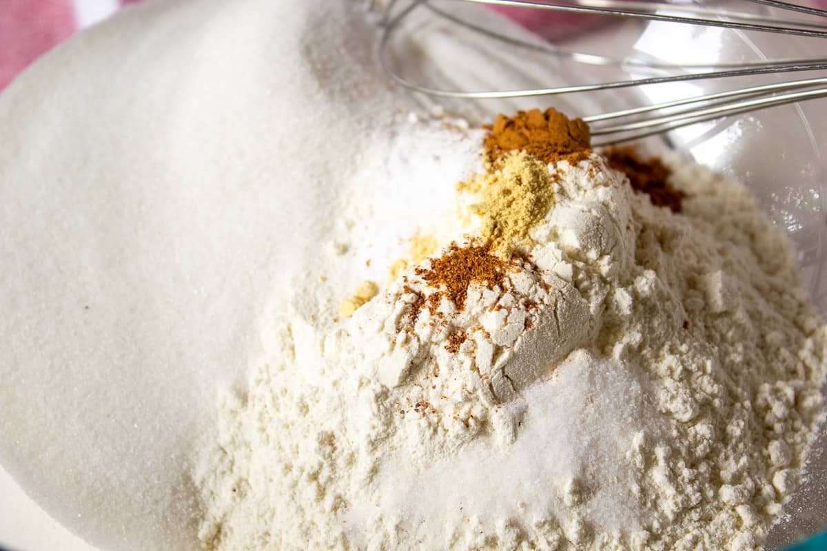 Flour and spices in a mixing bowl with a wire whisk.
