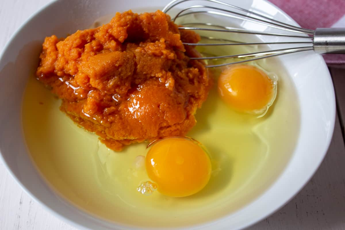 Eggs and pumpkin puree in a bowl with a wire whisk.