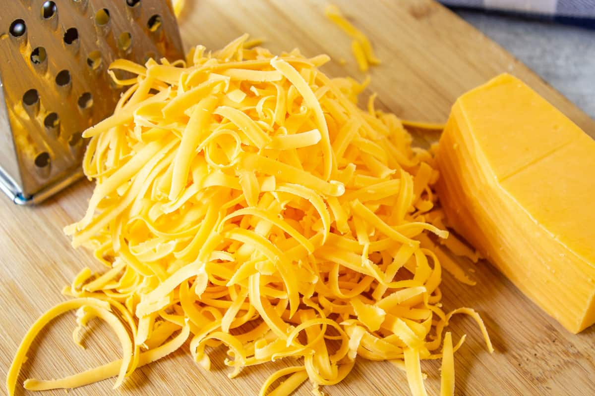 A pile of shredded cheddar cheese on a wooden board.