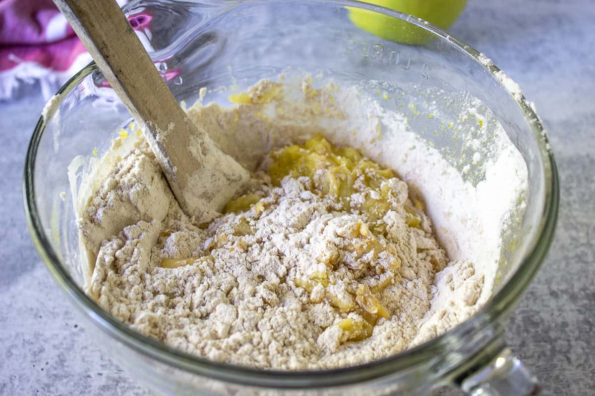 Flour mixture added to a wet mixture in a glass bowl.
