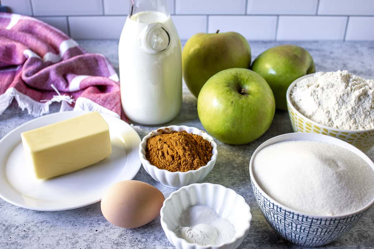 A variety of ingredients including apples, milk, butter, sugar and flour on a board.