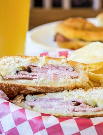 A ham sandwich on a hamburger bun cut in half.