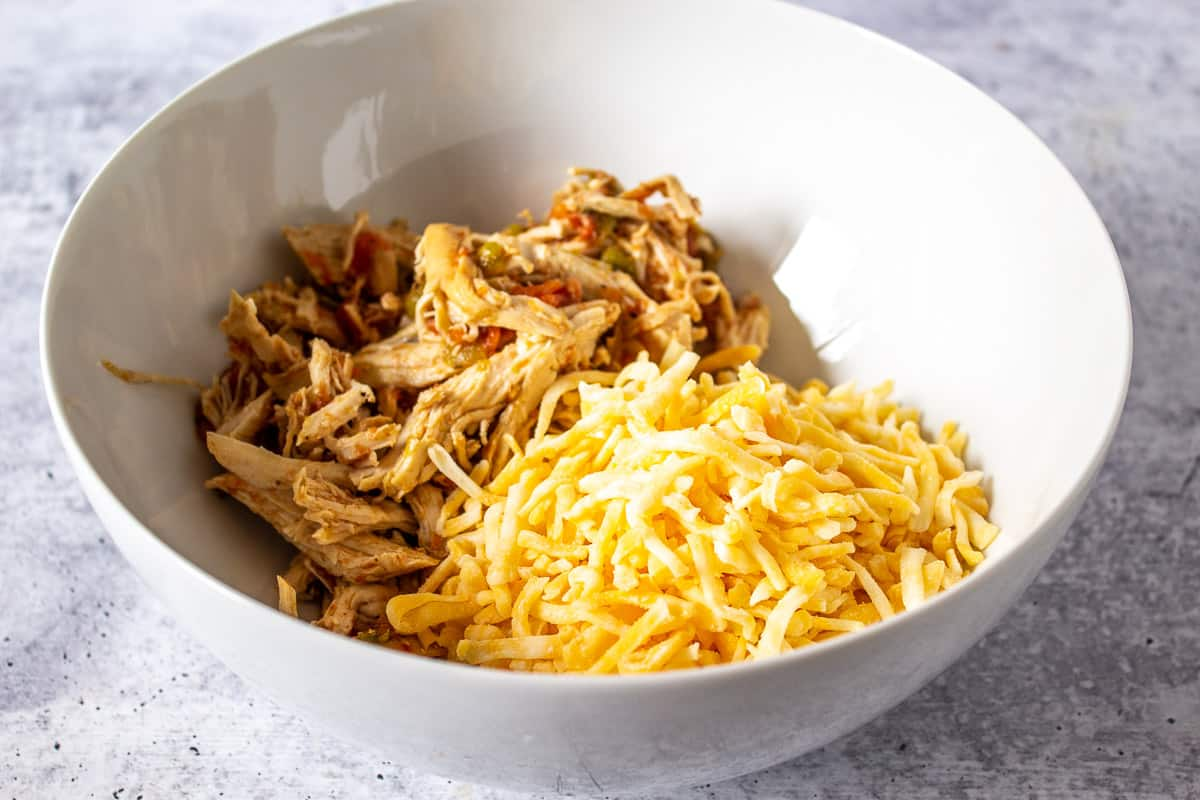 Shredded chicken and cheese in a bowl.