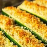Golden brown topping on long halves of zucchini.