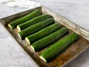 Zucchinis faced down on a baking sheet drizzled with olive oil.