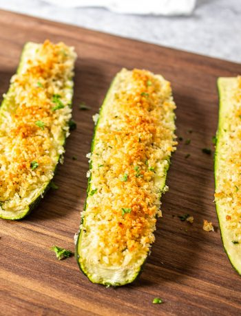 Roasted zucchini with browned parmesan cheese and bread crumbs on top.