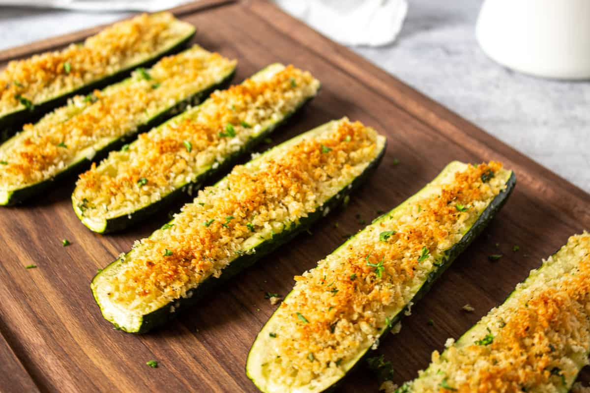 Oven roasted stuffed zucchini on a wooden cutting board.