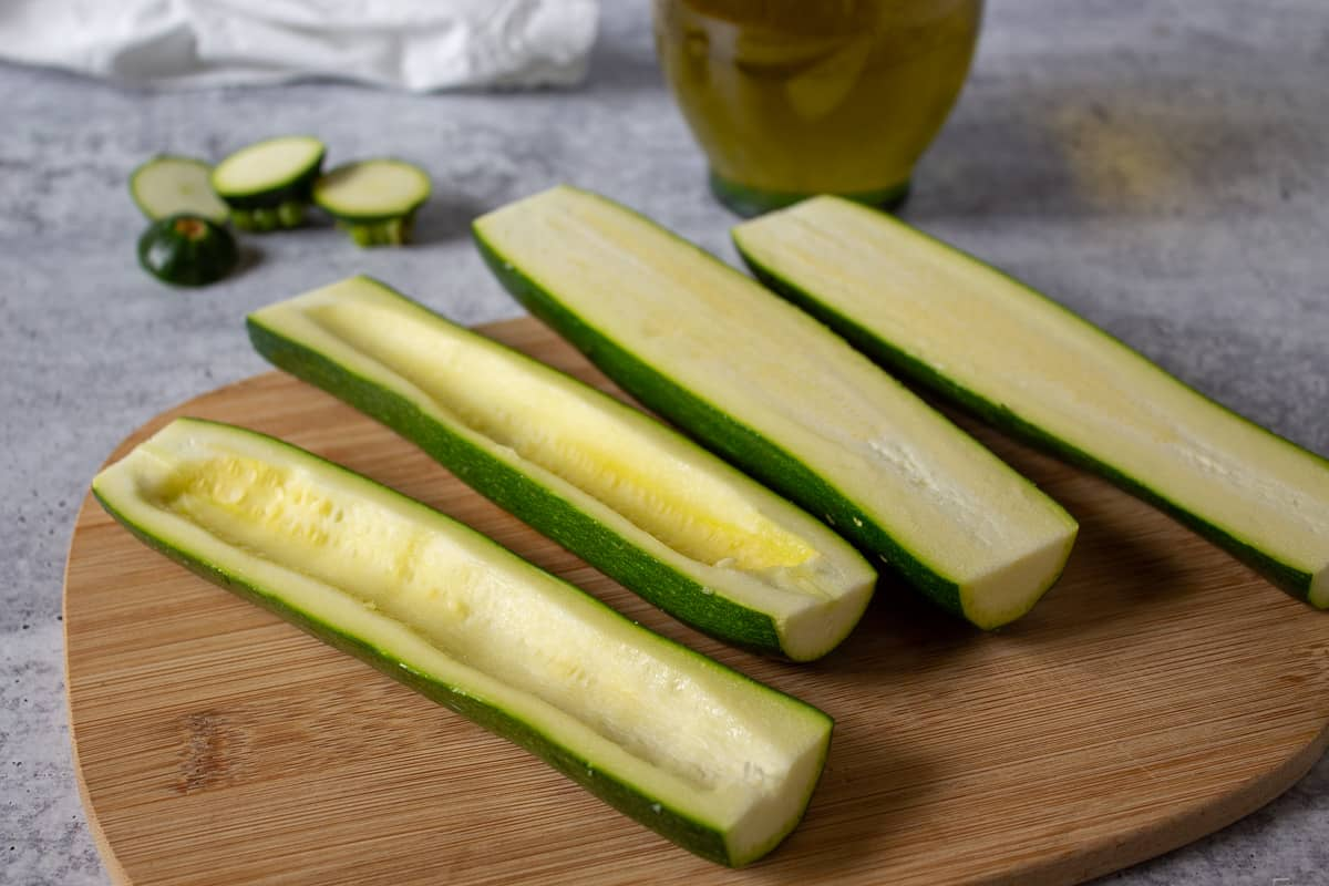 Zucchinis halved with the seeds scooped out.