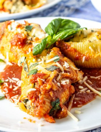 Three stuffed pasta shells with tomato sauce, parmesan cheese and fresh basil on top.