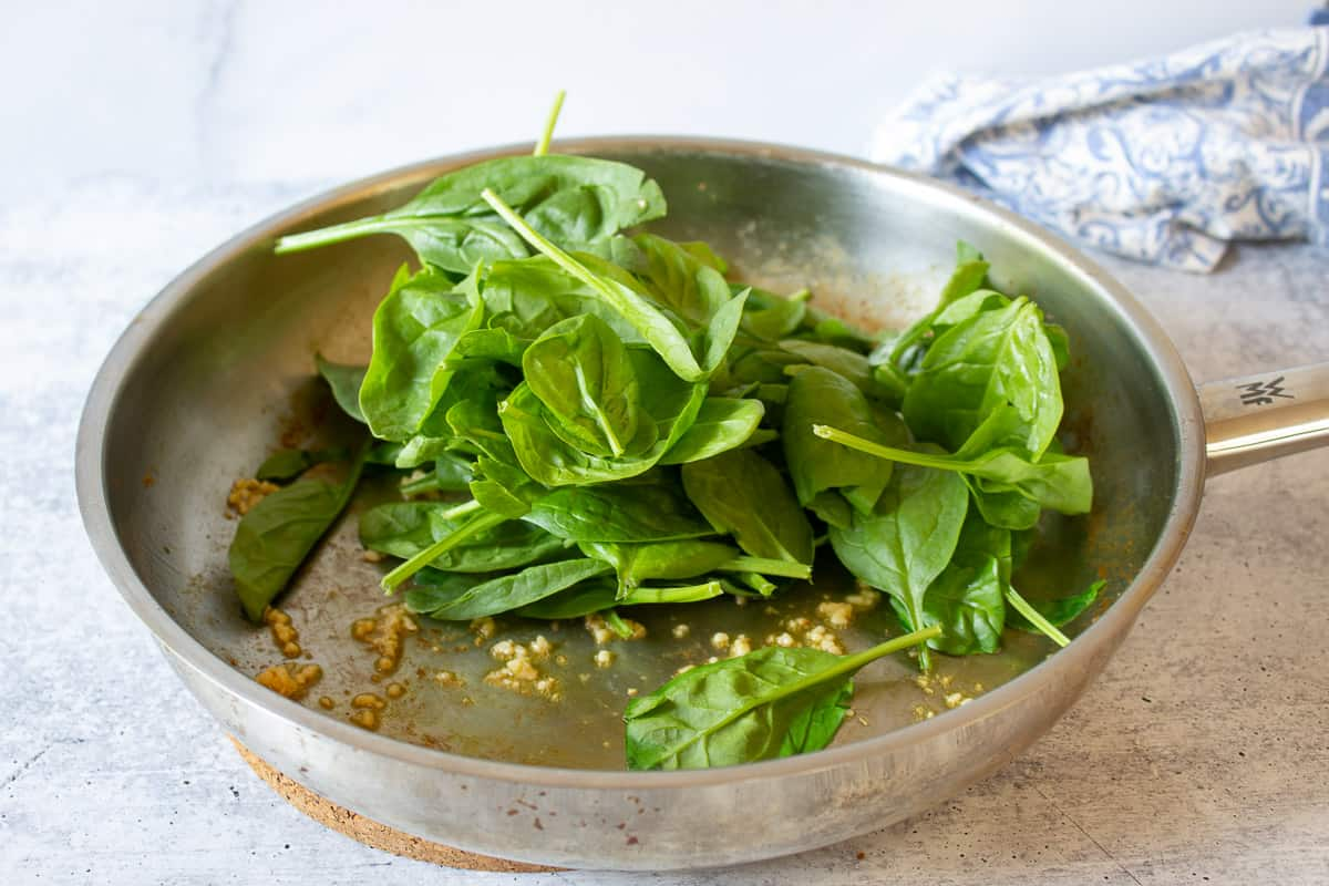 Fresh spinach in a pan with cooked garlic.