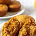 Bran muffins on a white plate with one muffin split in half and covered with honey.