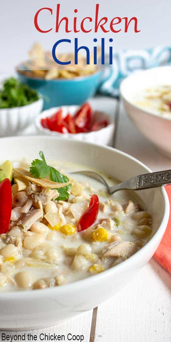 A white bowl filled with white chicken chili topped with fresh tomatoes.