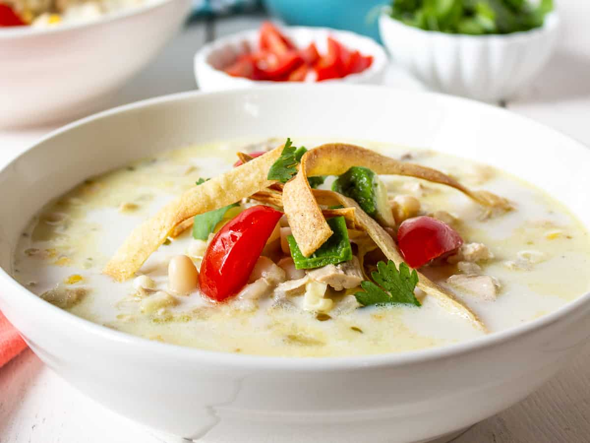 White chicken chili in a large bowl topped with fresh tomatoes, cilantro and tortilla strips.