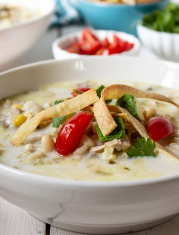 A bowl of white chicken chili topped with fresh tomatoes and tortilla strips.