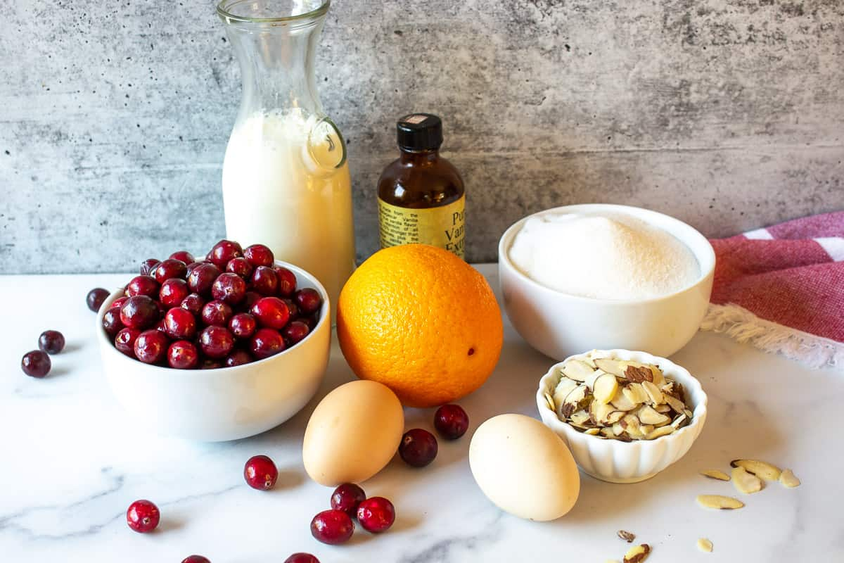 A display of cranberries, eggs, almonds, and an orange on a white surface.