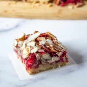 A cookie bar with cranberries and topped with almonds.